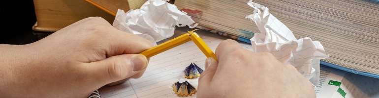 A photo of a pair of white-skinned hands holding a snapped yellow pencil in front of a collection of books. Beneath the hands are a notebook and some pencil shavings. There are also two scrunched up pieces of paper.